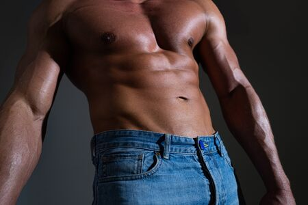 Sexy muscular man torso six packs. Muscular Gay sexy with six pack abs in studio. Muscular model man on dark background. Banque d'images