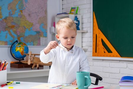 Kid is learning in class on background of blackboard. First school day. Kid 3 year old from primary school. Kids Science education concept.