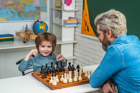 Educational games. Father and son. Fathers day. Games good for brain intelligence concept. Handsome father and son are playing chess while spending time together.