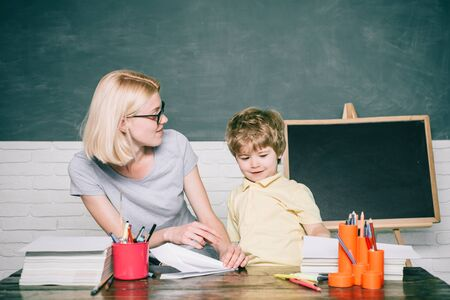 Back to school and happy time. Teacher helping young boy with lesson. Blackboard background - copy space. Preschooler.