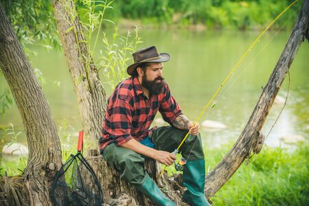 Man fishing on river. Sitting alone during the fishing process on the pier near the lake. Mature man fly fishing. Against the background of the water with a reflection of the forest.