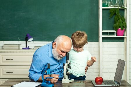 Concept of education and reading. Grandfather and grandson. Teacher is skilled leader. Thank You Teacher. Friendly child boy with old mature teacher in classroom near blackboard desk.