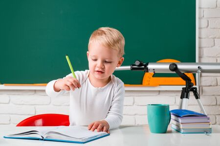 School kids against green chalkboard. Little student boy happy with an excellent mark. Happy cute industrious child is sitting at a desk indoors.