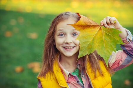 Happy child girl with autumn leaves outdoors. Cute little girl in autumn park. Little girl with autumn leaves in hand. Happy kid on a fall background.