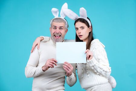 Easter couple having fun with rabbit ears. Easter egg hunting. Bunny couple hold board paper for text. Family celebrating easter.
