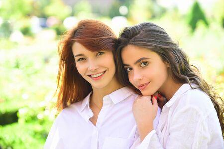 Weibliche Schönheit der Frauen. Menschenfreundschaftskonzept - lächelnde junge Frauen, die im Freien sprechen.