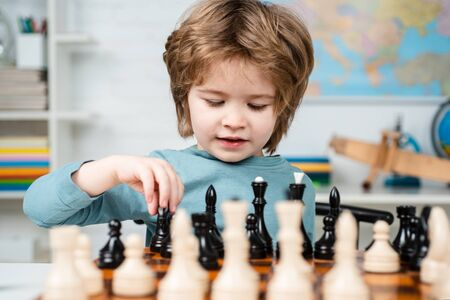 Kid Playing Chess. Kids educational games, child early development. Clever concentrated and thinking child while playing chess.