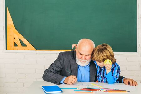 Grandfather talking to son. World teachers day. Educational process. Man with old teacher learning in class on color background.
