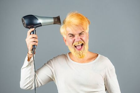 Dryer blond hair for a bearded hipster guy. Blonde Man with hairdryer, dryer or fen.