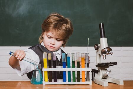 Kid is learning in class on background of blackboard. Knowledge day. Happy little scientist making experiment with test tube