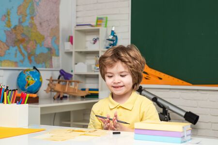Cute little preschool kid boy with teacher study in a classroom. First school day.