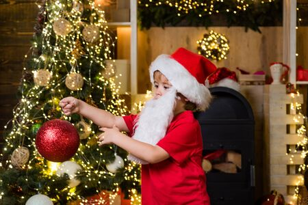 Cute child boy decorating Christmas tree. Happy child with Christmas bauble. Cute little kids celebrating Christmas. Happy cute child in Santa hat with bauble have a Christmas