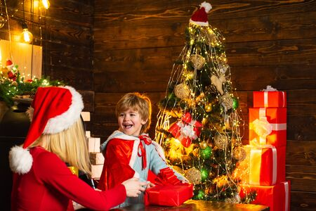 The morning before Christmas. Christmas kids - happiness concept. Christmas kids. Home Mother is giving a Chritmas gift to her happy son. Stock Photo