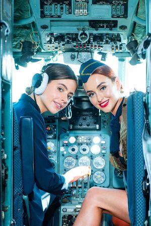 Two beautiful women pilot wearing uniform. Looking at camera through the cockpit. Pilots in cockpit. Girls looking at camera. Happy and successful flight. Couple Women Pilot Sitting in Cabin. 免版税图像