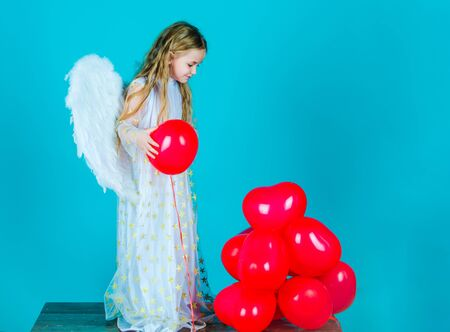 Kids Valentines Day. Looks like an angel. Angel kid with blonde curly hair. Cute child girl in white dress standing over color background. Portrait of beautiful angel little girl with angels wings. 스톡 콘텐츠