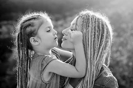 Happy family and lovely mom and daughter spend time together - mothers day. Mother and daughter. Happy mother and daughter hugging over sun lights background. Stok Fotoğraf