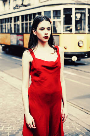 Beautiful brunette young woman wearing dress and walking on the street. Posing in the city wearing red dress. Gorgeous young model woman with perfect hair. Young woman posing.