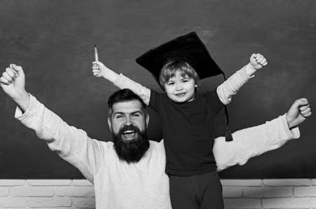Elementary school teacher and student in classroom. Yay. Smiling broadly. Woohoo. Family generation. Dad and son having fun in Time and its effects. Two generations.