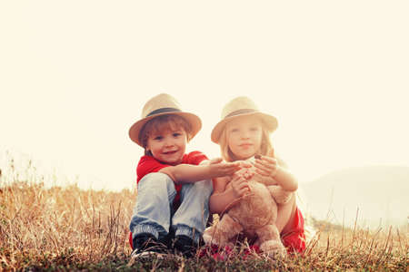 Walk on countryside. While having fun outdoors. Close friends. Posing outside. Children outdoors in nature. Charming boy and girl. Smiling cute little children in sunny day. Stockfoto