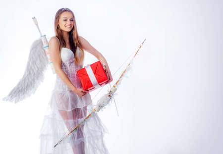 Cute little female cupid shoots a bow. Arrow of love. Little goddess with white wings alone on blue sky background. Teen angel. Cute teen girl. Angel children girl with white wings.