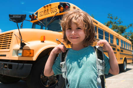 Child School concept. Portrait of Happy school child. Child from elementary school with bag on school bus backgroung.