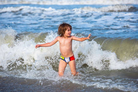 Little boy playing in outdoor jumping into water on summer vacation on tropical beach island. Happy child playing in the sea.