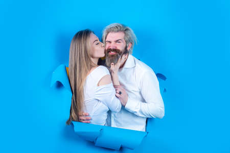 Fashionable happy couple on blue background. Young couple kissing through paper. Surprised man and woman looking through wall.