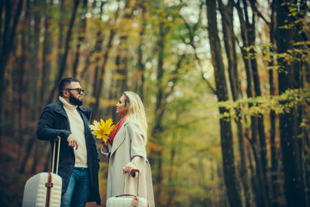 Beautiful couple over autumn background. Young couple outdoors at the park on beautiful autumn day. Adventure, travel, tourism, hike and people concept. Couple walking with yellow leaves.