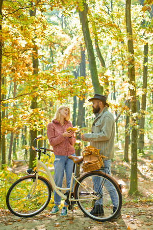 Autumnal happy couple in love enjoy sunny warm day at forest. Active lifestyle and cycling activity. Hipster lovers relax outdoor. Blonde lovely woman in sweater and bearded man in hat.