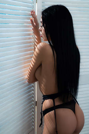 Sensual girl. Naked girl sitting in a beautiful position. Interior hotel room with large windows.