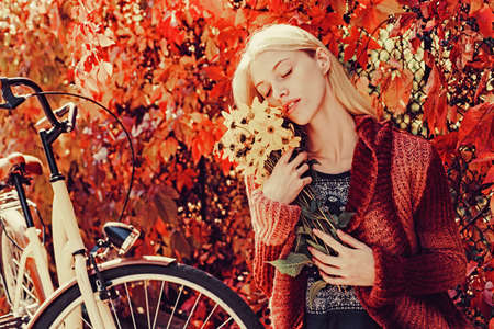 Autumn fashion concept. Cute girl in good mood posing in autumn day. Autumn woman. Autumnal trend and vogue. Banco de Imagens