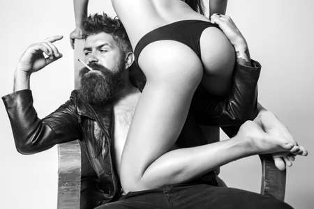 Beautiful female body in black lingerie with muscular man. Young beautiful couple in love. Casual style. Brunette girl in a black panties. Confident man in smart clothing. Smoking.