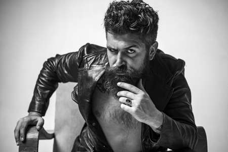 Brutal bearded fashionable man with serious face sitting in chair and looking at camera. Macho man Casanova attracting women. Sexy rich shirtless millionaire man with leather jacket. Stock Photo