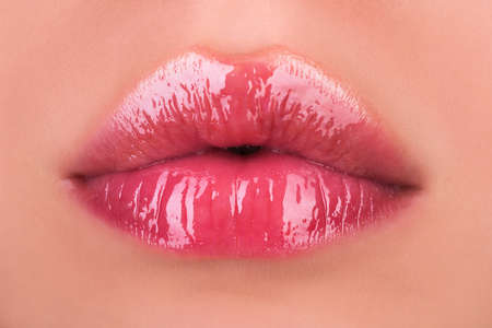 Sexy female lips with pink lipstick. Sensual womens open mouths. Red lip with glossy lipgloss. Seductive lips of a young woman.