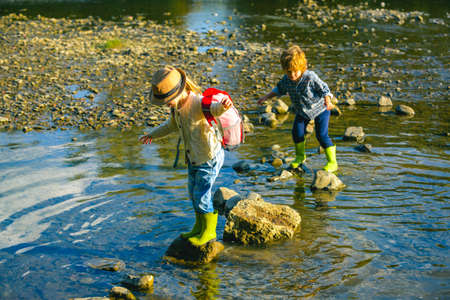 Little sister and brother playing in the river in the nature. Toddler kid play with sibling holding hands and playful. Cute girl and toddler Family with children. Love, trust and tenderness. Foto de archivo