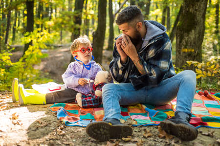 Happy family walking at autumnal park. Bearded dad catched a cold and sneeze at napkin. Father play with his little child a doctor game. Autumn seasonal cold concept.