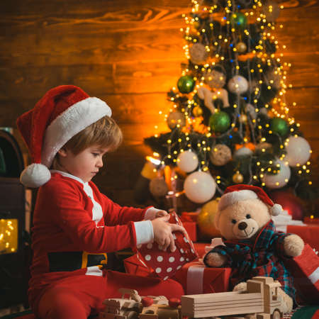Happy new year. Christmas interior. Kid having fun near Christmas tree indoors. Winter delivery service for kids.