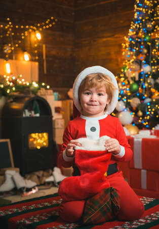 Child with a christmas socks on wooden background. Happy little smiling boy is wearing Santa clothes. Happy kid having fun with gift. Christmas tree bachground.