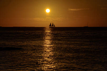 Sailboat on the ocean at sunset. Yacht against sunrise background. Beautiful sunset over ocean with boat sailing.
