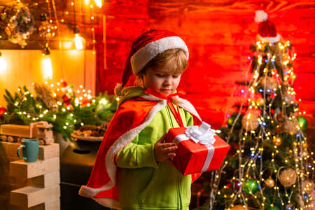 Happy little boy by the Christmas tree looking at his Christmas gift. Little kid is wearing Santa clothes. Foto de archivo