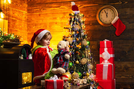 Happy child holding a red gift box with both hands. Christmas Celebration holiday. Happy little child dressed in winter clothing think about Santa near Christmas tree.