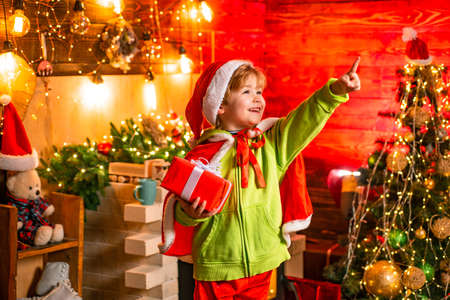 Happy little boy child with present or gift box indoors. Funny kid holding Christmas gift. Gift emotions. Happy child with Christmas gift. Foto de archivo