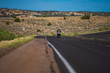 Biker on motorbike, Route 66. American landscape with asphalt road to horizon. Motorbike on the road riding.
