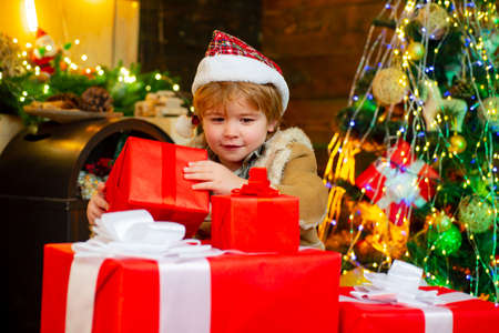 Cute little child is decorating the Christmas tree indoors. Cute little kids celebrating Christmas. Cute little child near Christmas tree.