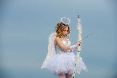 Cupid cute girl with a bow. A beautiful teen with blonde curly hair and a bow and arrow as cupid - Valentines Day. Bow and arrow. Festive Art Greeting Card