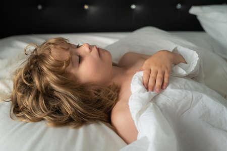 Boy kids sleep in bed. Sleeping Child lies in bed with eyes closed. Standard-Bild