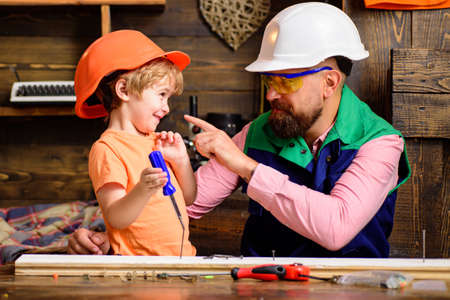 Tools construction. Father teaching little son to use carpenter tools and hammering. Father helping son at workshop.