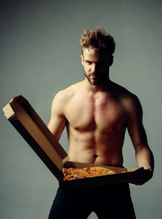 Strong brutal bearded man holding an italian tasty pizza isolated at gray background. pizza deliver with muscular torso. Handsome hungry man with food fetish.