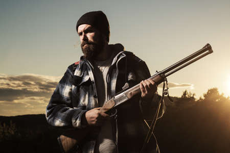 Hunter with a hunting gun in the autumn forest. Rifle hunter in Sunset. Hunter in the autumn fall on hunting season.