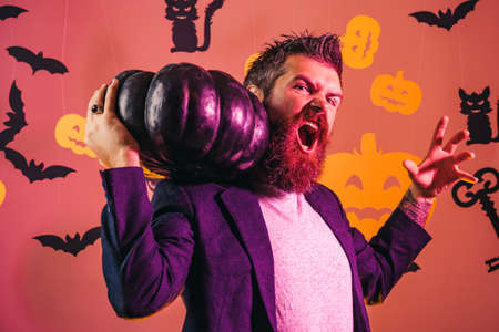 Halloween man. Hipster with bloody beard hold pumpkin. Scary man with horror face, facial expression. Stock Photo